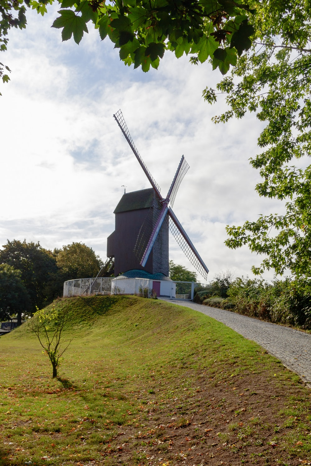 windmill building beside road and near trees during day