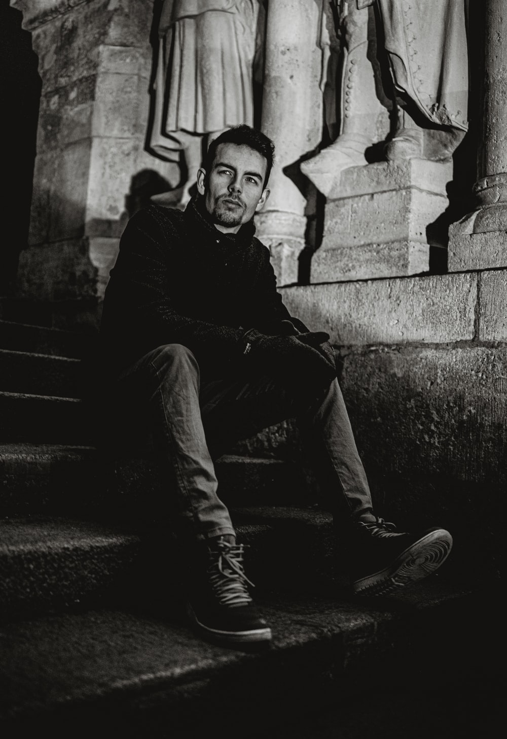 grayscale photo of man sitting on staircase