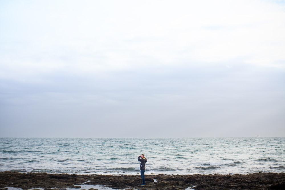 man standing on shore under white sky