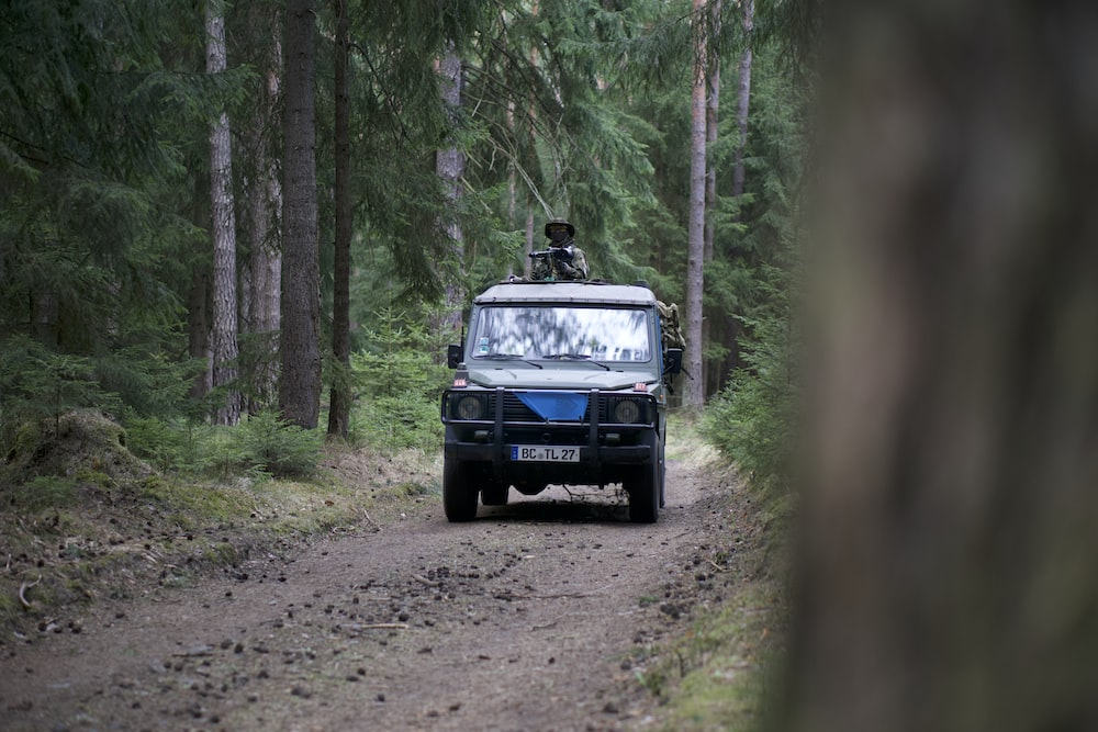 black car on dirt road near trees during day