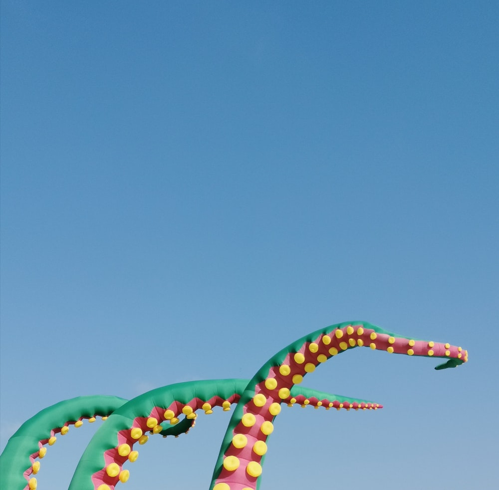 red, yellow, and green octopus tentacle inflatables under blue sky