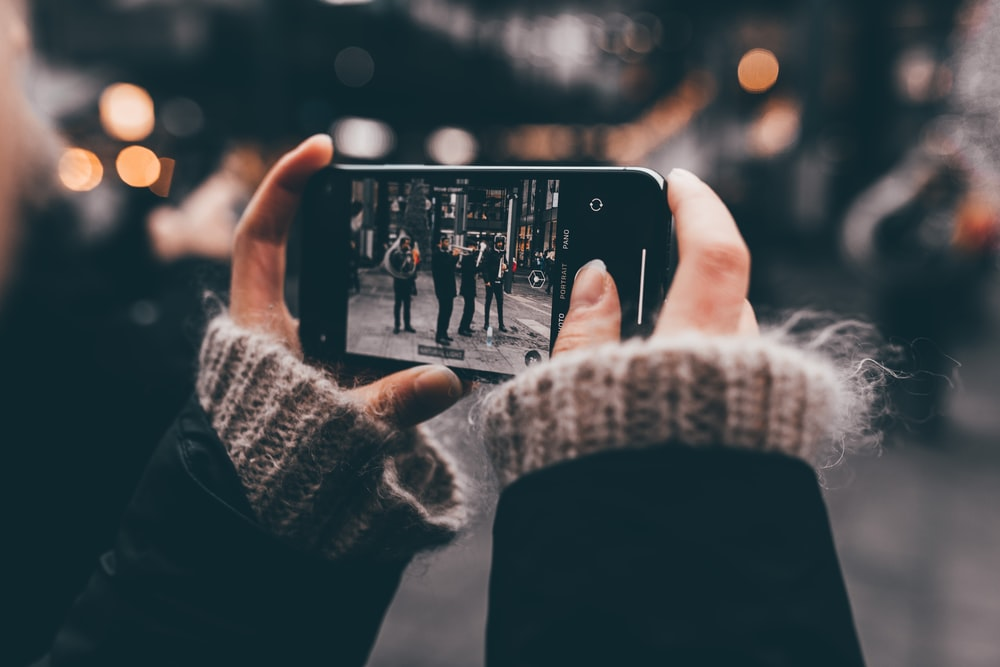 person using smartphone camera on people during day