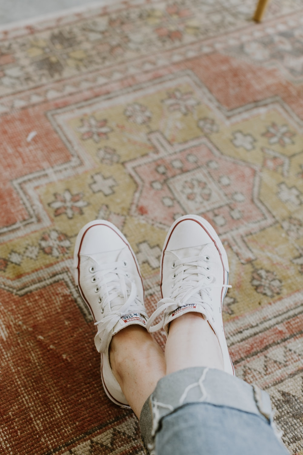 person wearing white Converse sneakers