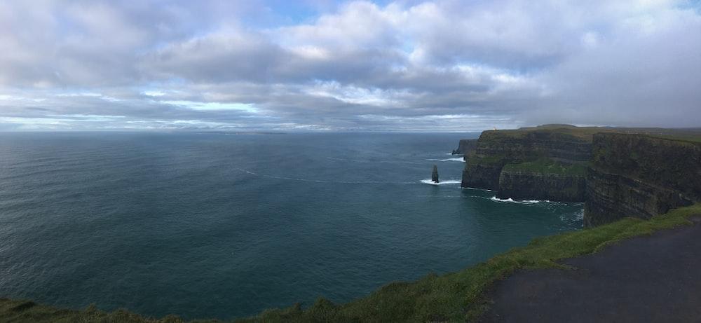 rocky cliff facing ocean under cloudy sky