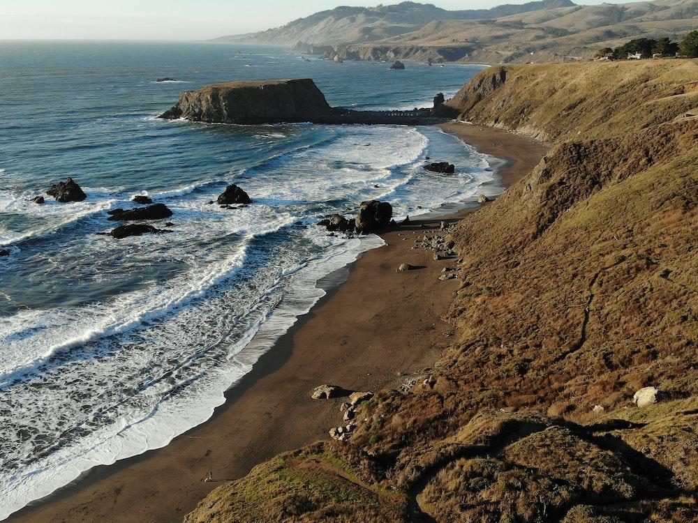 bird's eye photography of rock formation on shoreline