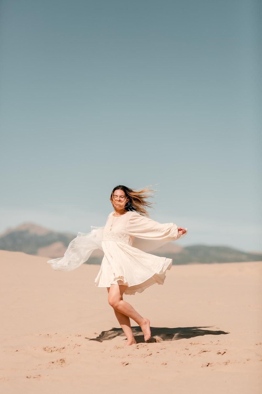 woman in white dress standing on desert