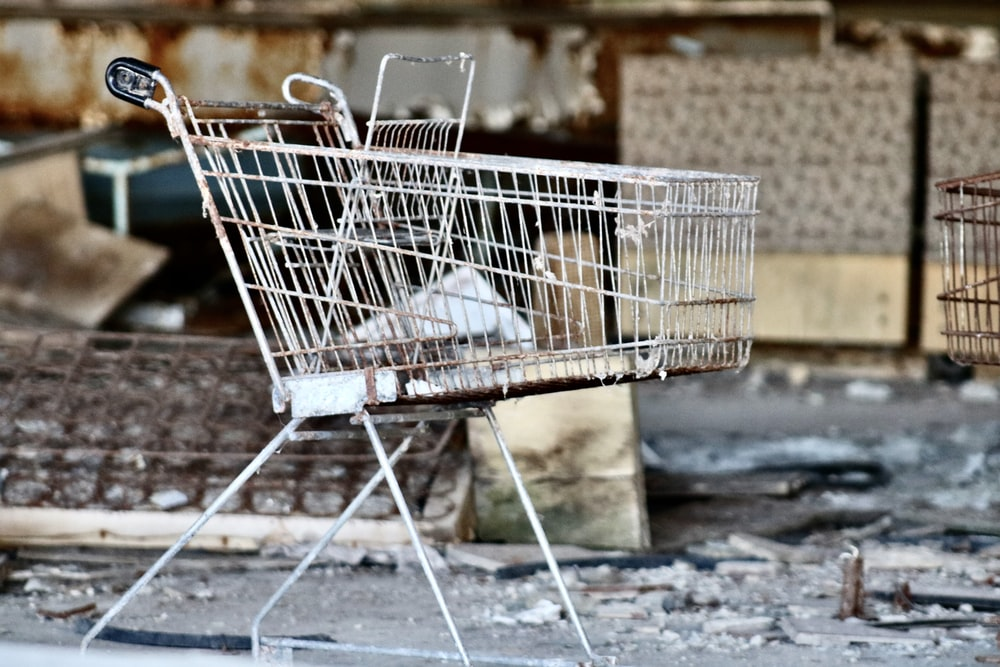 gray metal shopping cart by concrete wall at daytime