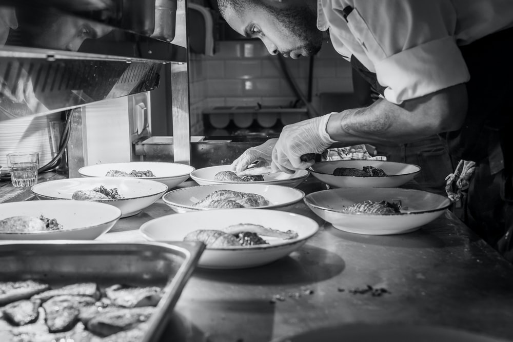 grayscale photography of person doing plating of dishes