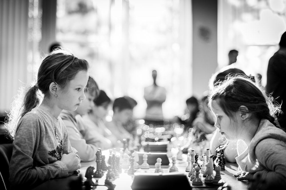 grayscale photography of children sitting while playing chess
