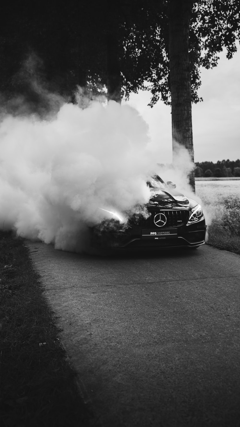 Mercedes-Benz on road covered with smoke during daytime