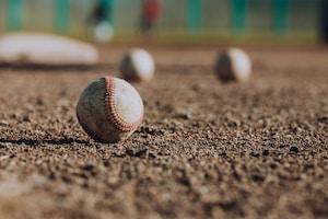 selective focus photography of white baseball balls on ground
