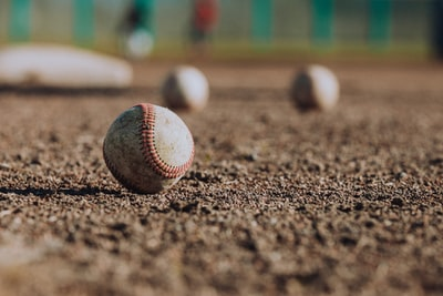 selective focus photography of white baseball balls on ground baseball zoom background