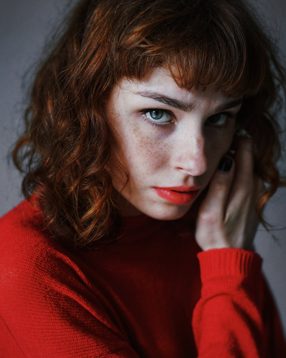 woman wearing red crew-neck sweater looking straight