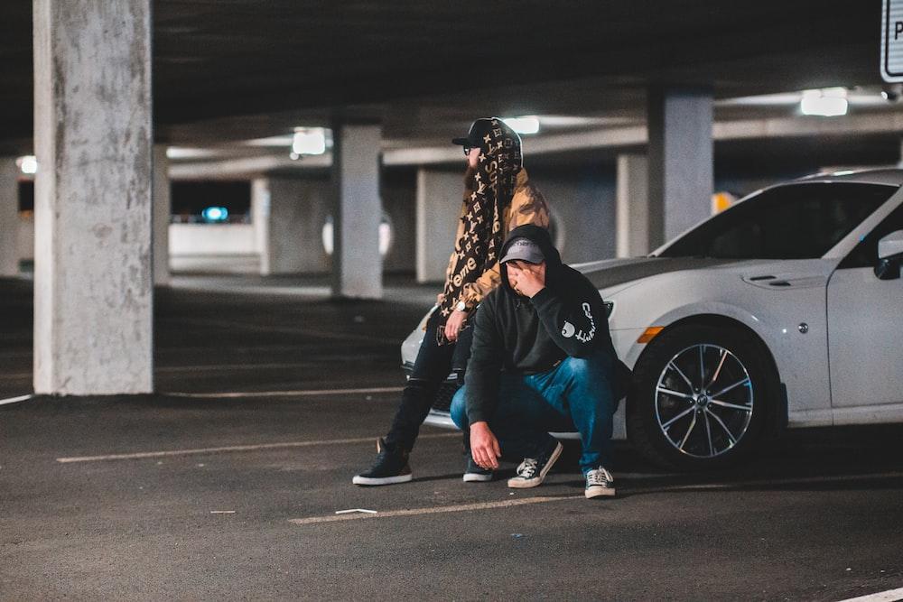 man crouching beside man sitting on car's hood