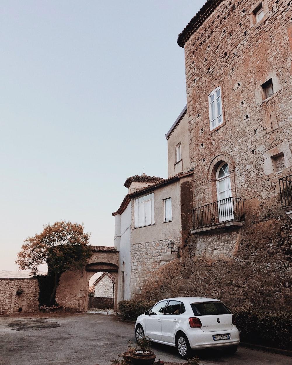 white 3-door hatchback near house