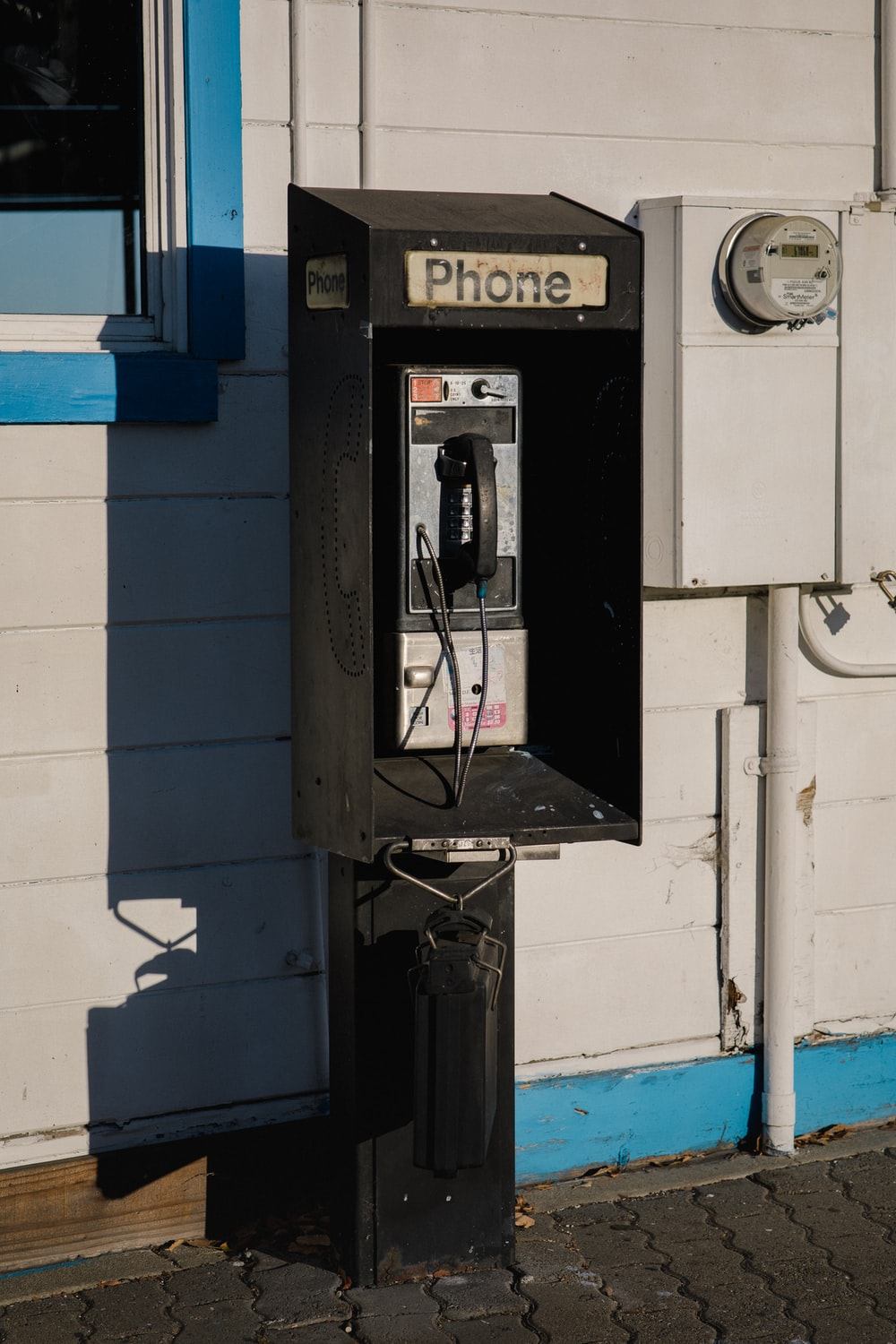 black coin telephone during daytime