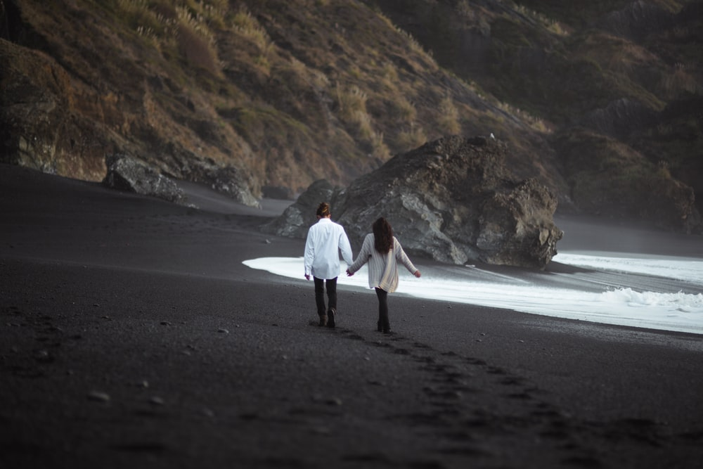 man and woman holdings hand together while walking on beach