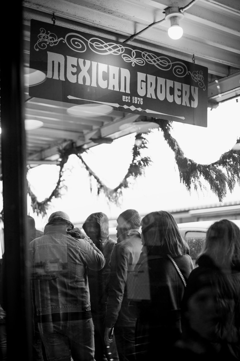 grayscale photography of people standing outside Mexican Grocery building