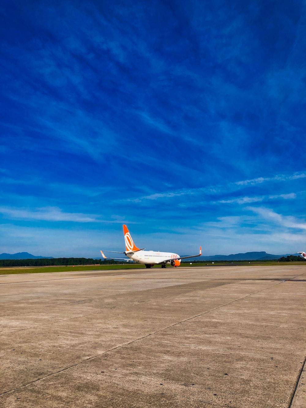 white and orange passenger airplane landing under blue and white sky