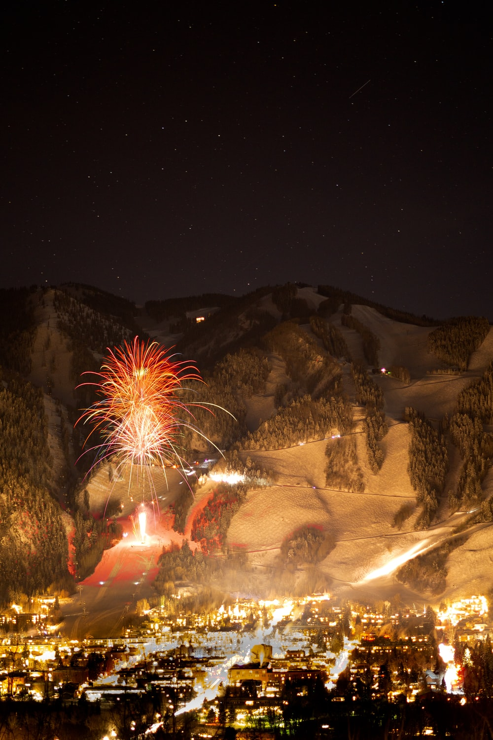fireworks display above buildings viewing mountain