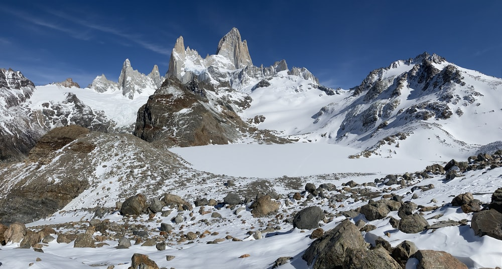 rock formations on field and mountain covered with snow under blue sky