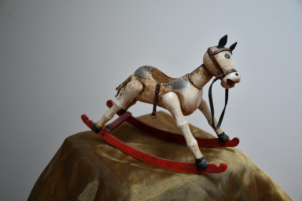 horse rocking toy on brown textile