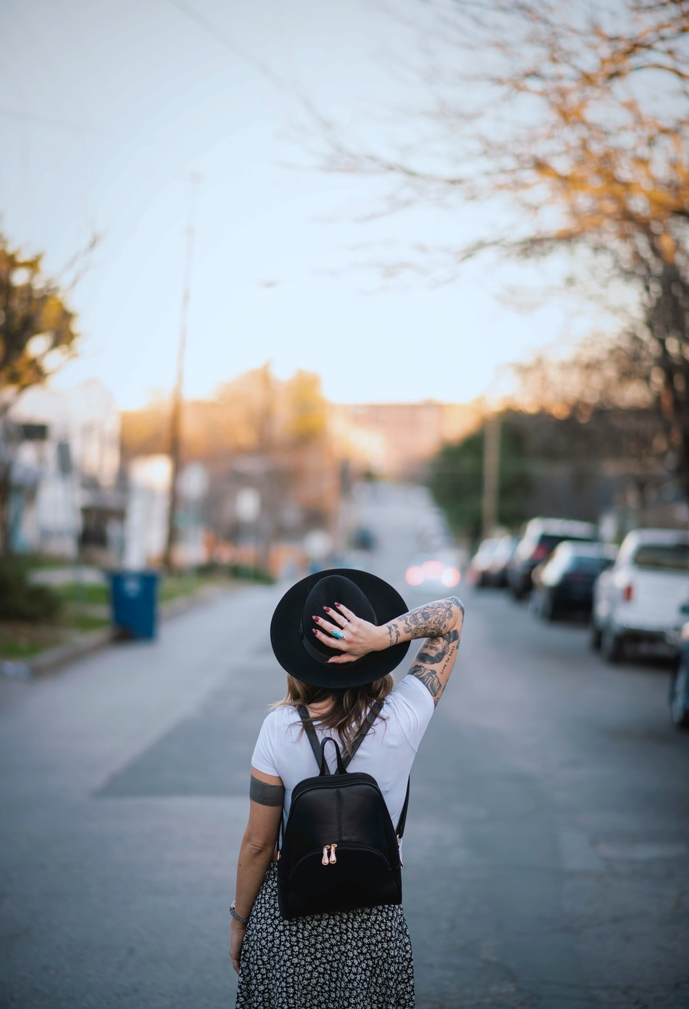 woman wearing white crew-neck t-shirt and black hat with black leather backpack standing while facing back on road during daytime
