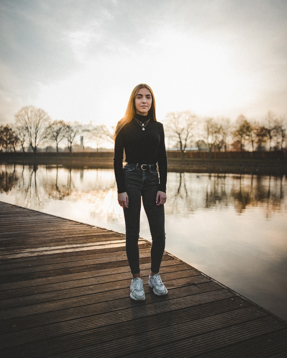 woman in black long-sleeved top and jeans standing on wooden dock during golden hour