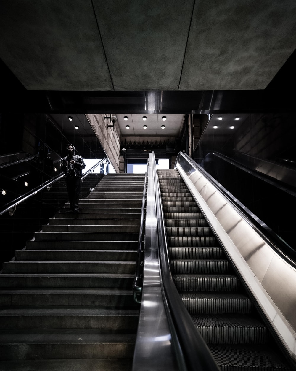 person wearing hooded jacket standing on concrete stairs near escalator