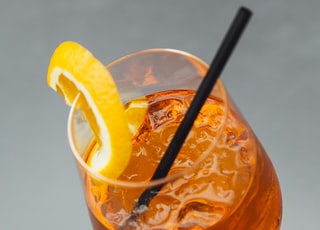 3/4 filled long-stem glass cup with straw and slice of orange