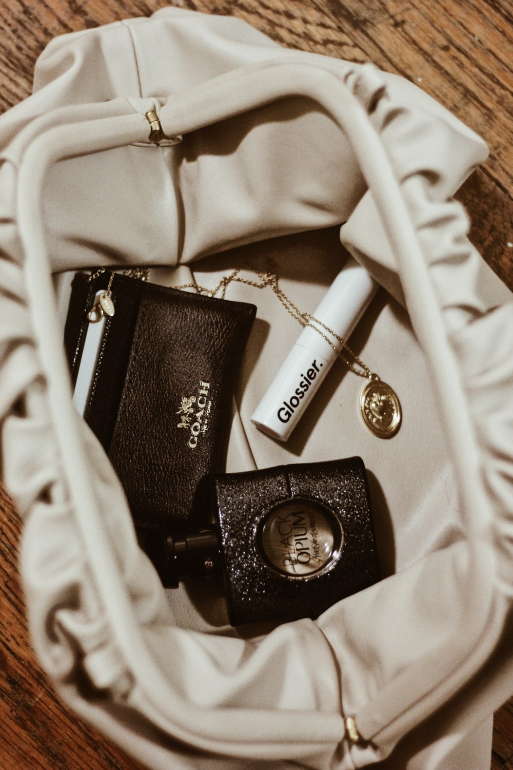 gold-colored necklace near lip gloss, wallet, and spray bottle