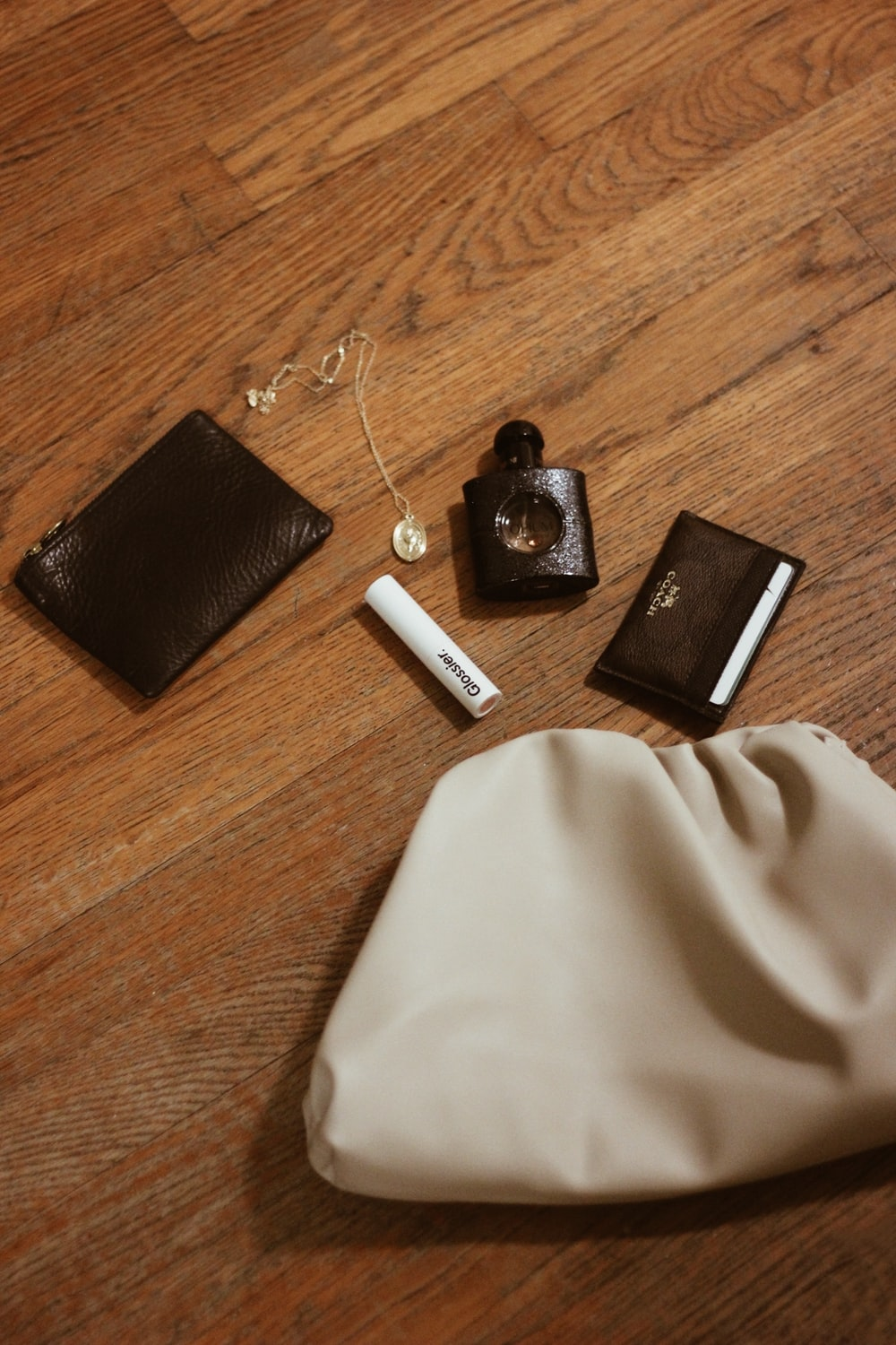 black wallet near spray bottle, necklace, and coin purse
