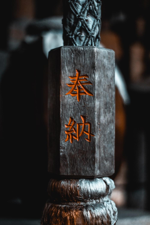selective focus photography of gray Kanji script wood