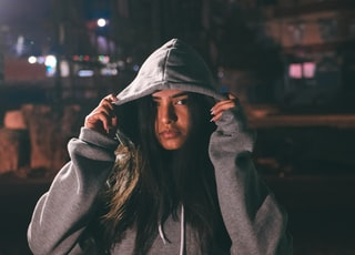 woman in hoodie while both hands holding the hood