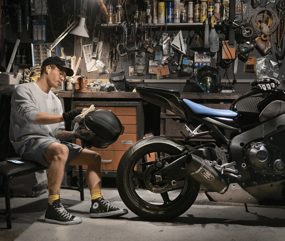 man wiping motorcycle helmet by motorcycle