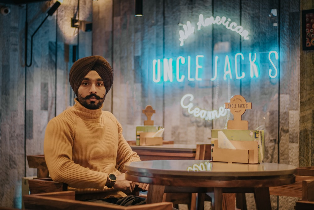 selective focus photography of man sitting beside Uncle Jack's sign