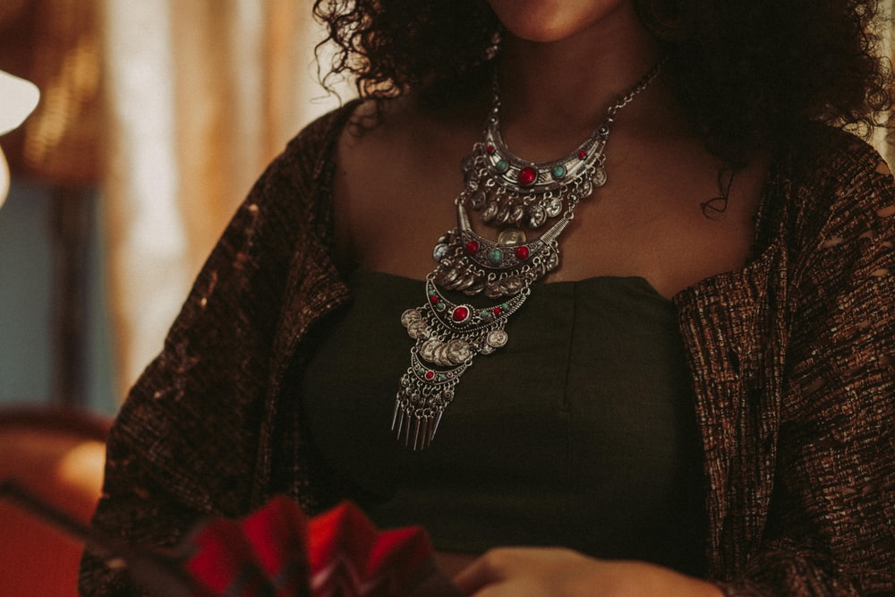 woman wearing silver-colored bib necklace