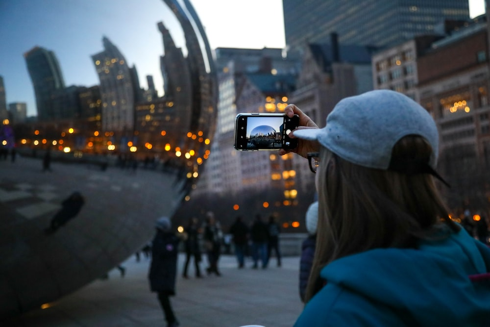 woman taking a picture of sphere monument