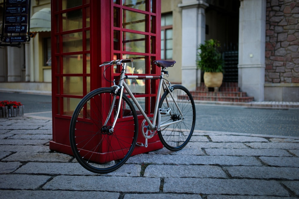 gray road bike leaning on red telephone booth