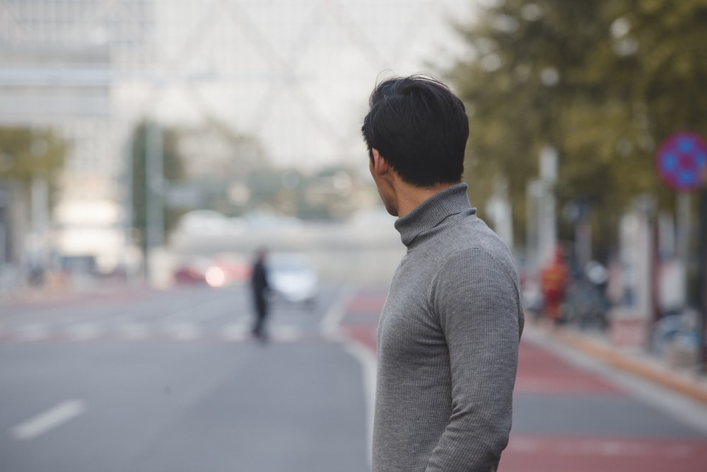 man gray turtleneck shirt standing road during daytime