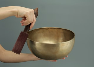 person holding brass-colored song bowl set