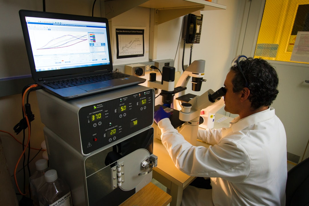 DNA Genotyping and Sequencing. A technician observing cells under a microscope at the Cancer Genomics Research Laboratory, part of the National Cancer Institute's Division of Cancer Epidemiology and Genetics (DCEG).