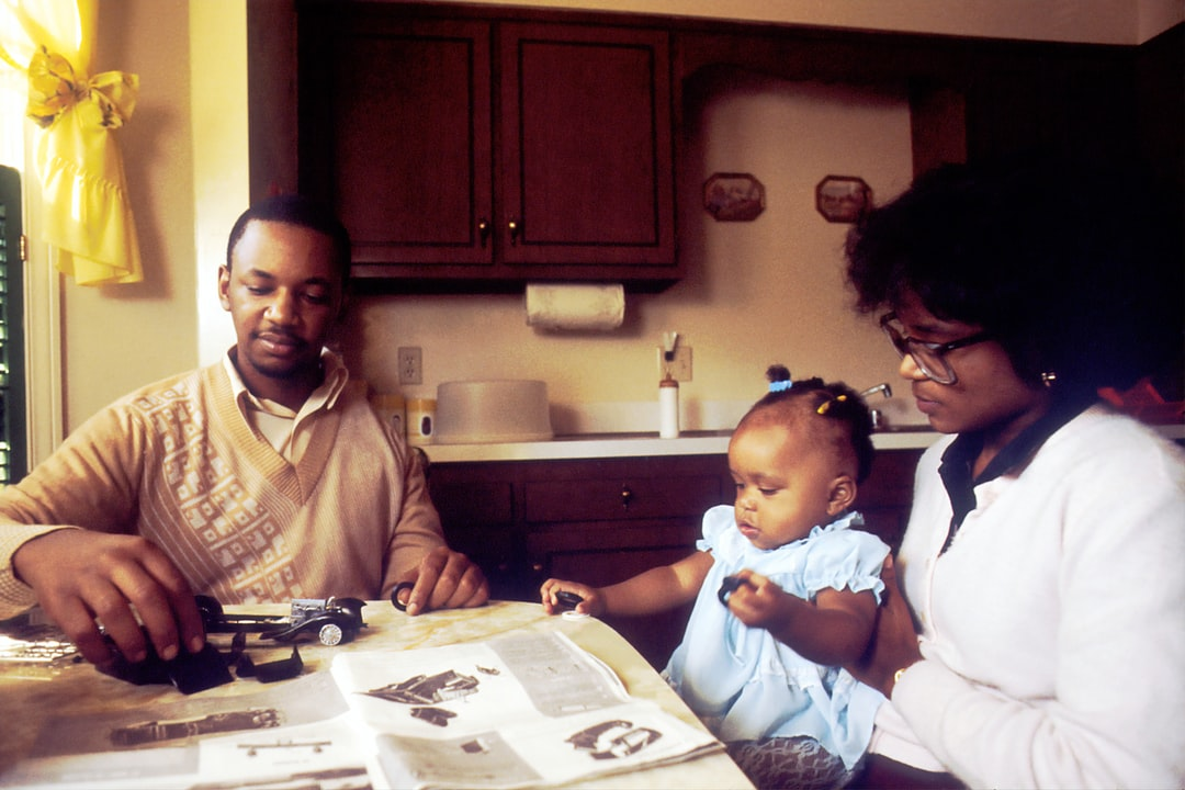 Family Sitting at Kitchen Table. An African American man with his wife and daughter at the kitchen table. He is assembling a Rolls Royce model car indicating the digital facility he maintains. He was diagnosed as having osteogenic sarcoma in his upper left arm. Surgeons performed a new procedure, implanting a metal rod in place of the cancerous bone. Since the muscle and tendon were saved he has the use of this arm.