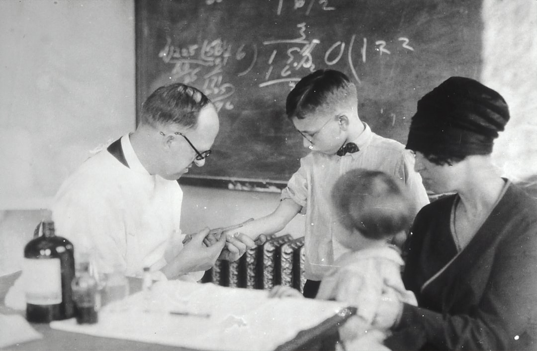 Schick Test 1915. Photo of young boy receiving the Schick Test from a doctor. Boy is accompanied by mother and younger sibling (1915). The Schick Test is a measure of immunity to diphtheria.