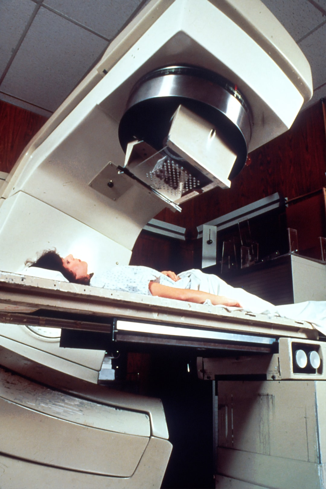 Woman Readied for Radiation. A Caucasian adult female patient being readied for radiation therapy. She is lying on a table, covered with a white cloth.