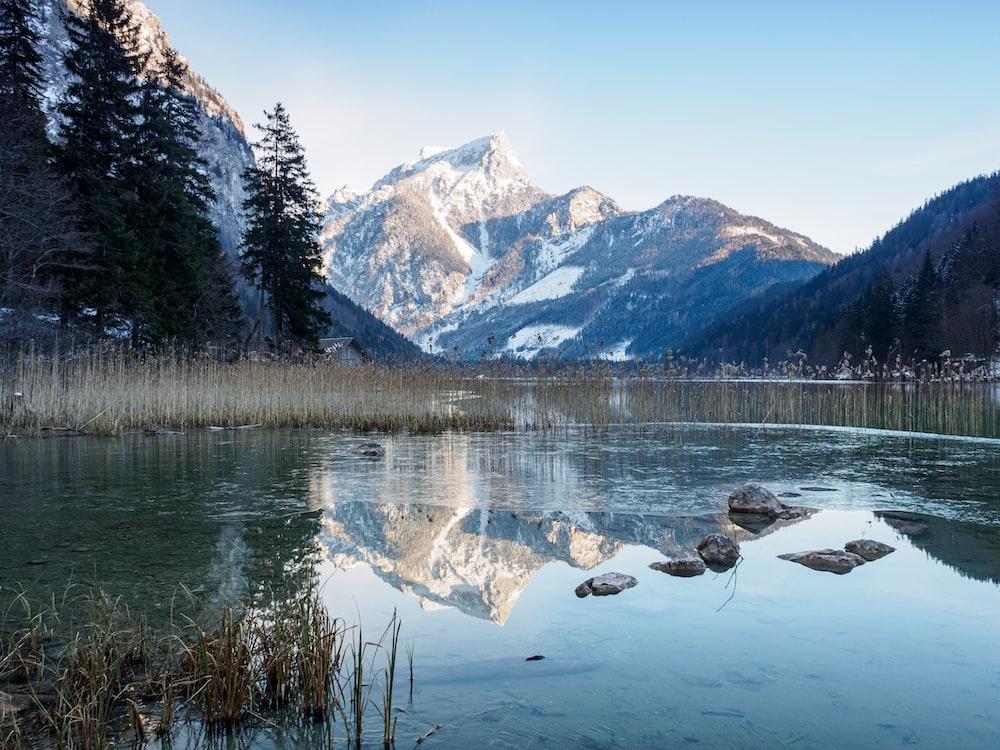 lake under mountain during daytime