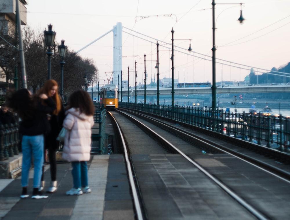three person standing beside train rail