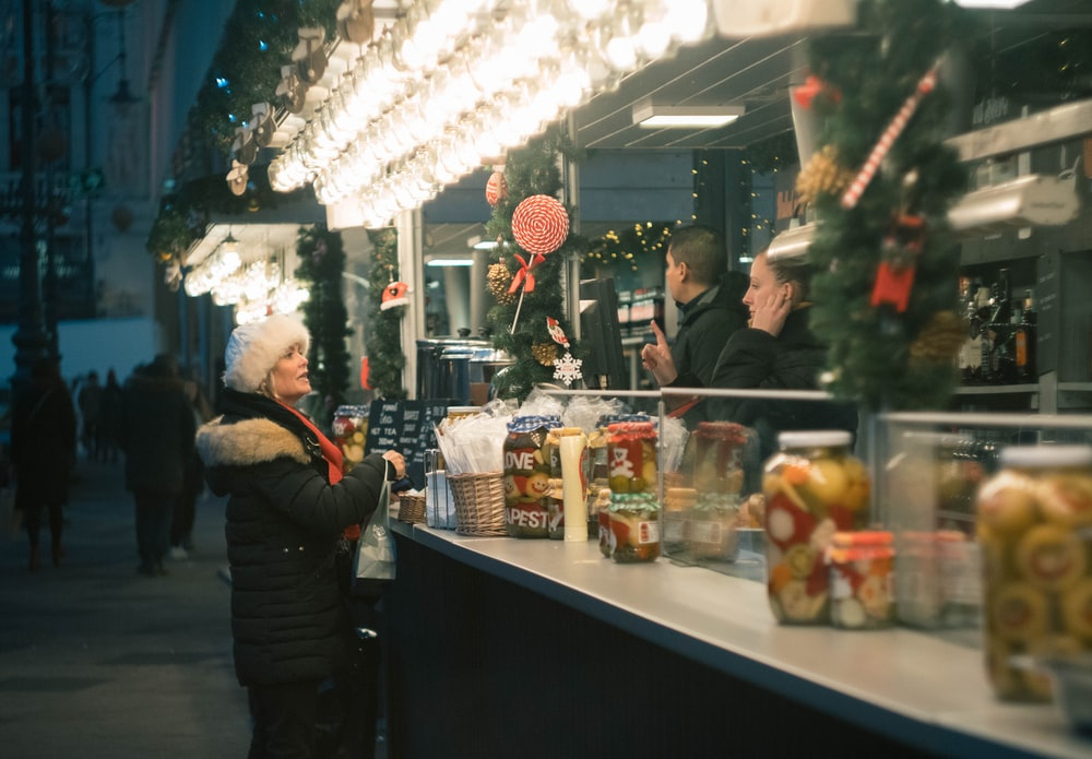 woman in black and white winter coat standing beside stall during nighttime
