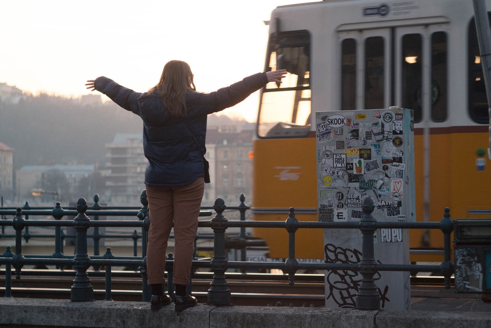 woman standing while raising hand in front of bus