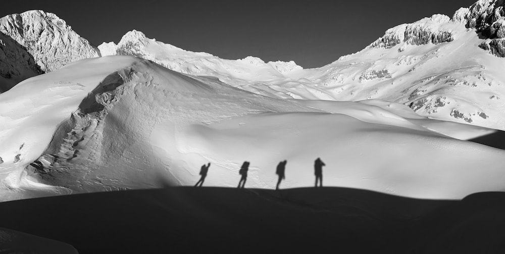 grayscale photography of four people walking near snowy mountain